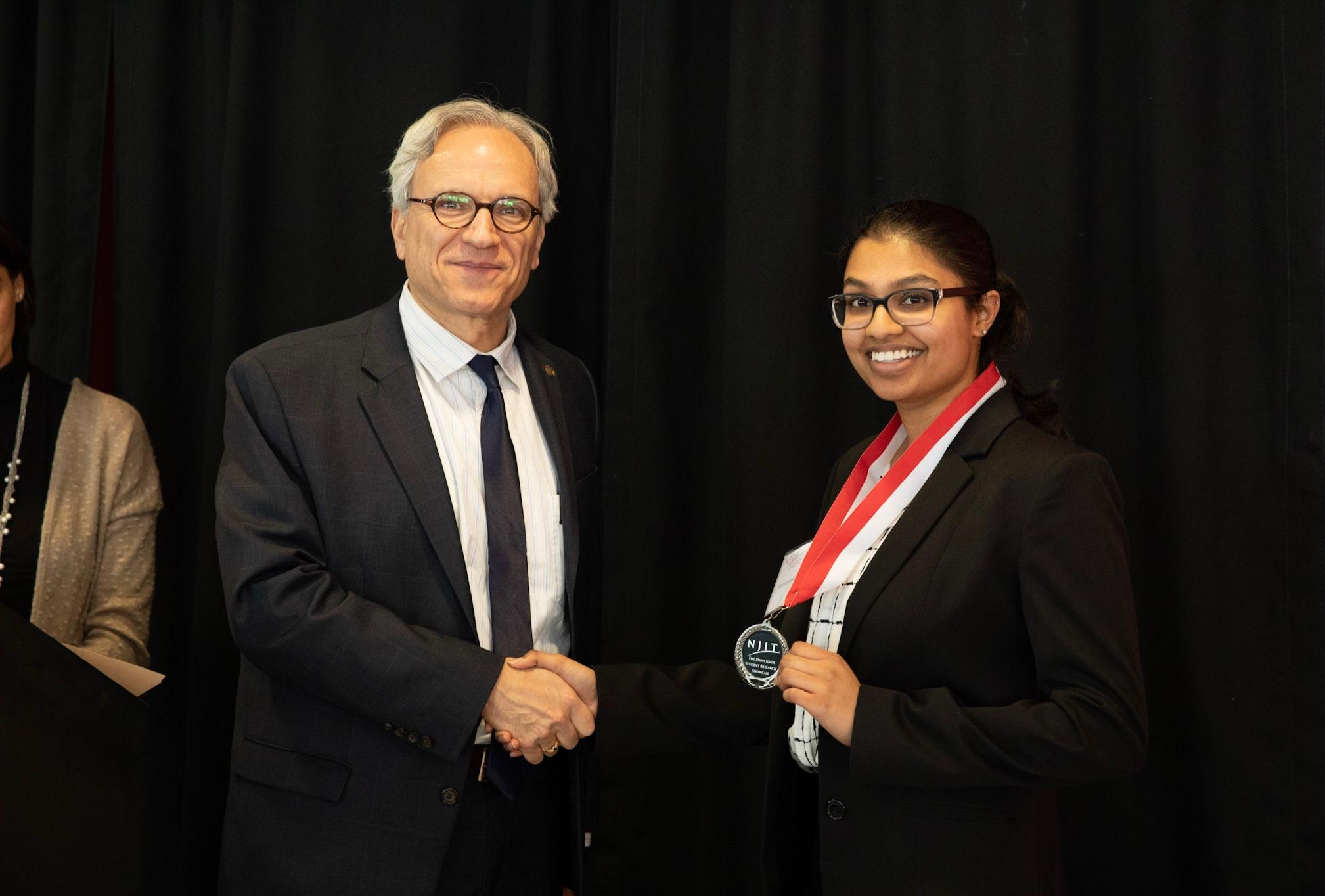 Biology sophomore and student at Albert Dorman Honors College, Geetasravya Vegunta, collects her award alongside NJIT Provost Fadi P. Deek.