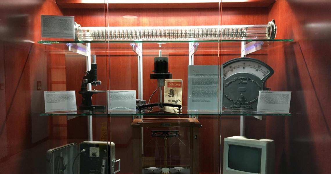 NJIT Distributed Technology Museum's first 7-piece exhibit displayed in Fenster Hall (Top Shelf: York-Scheibel Column; Middle Shelf, Left: 1947 Bausch & Lomb optical microscope; Middle Shelf, Center: Brookefield Viscometer; Middle Shelf, Right: Weston Sta