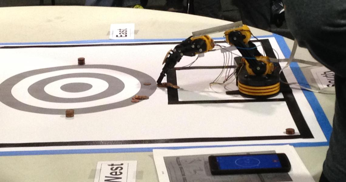 A robotic arm picks up pennies at the 2017 New Jersey Science Olympiad, hosted at NJIT.