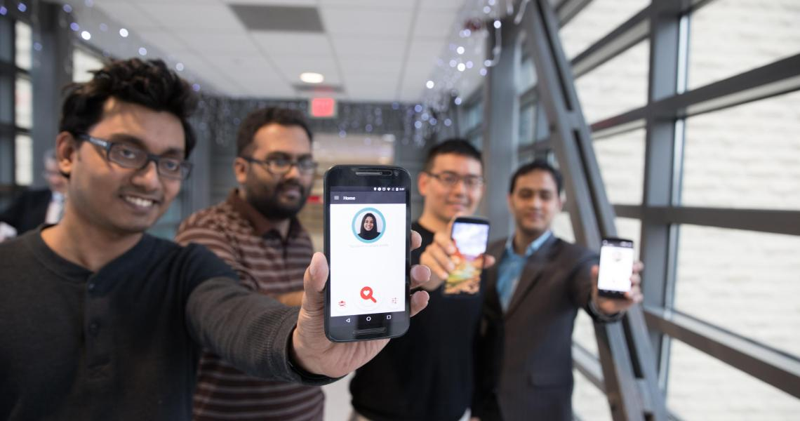 four students hold up smartphones featuring FaceDate