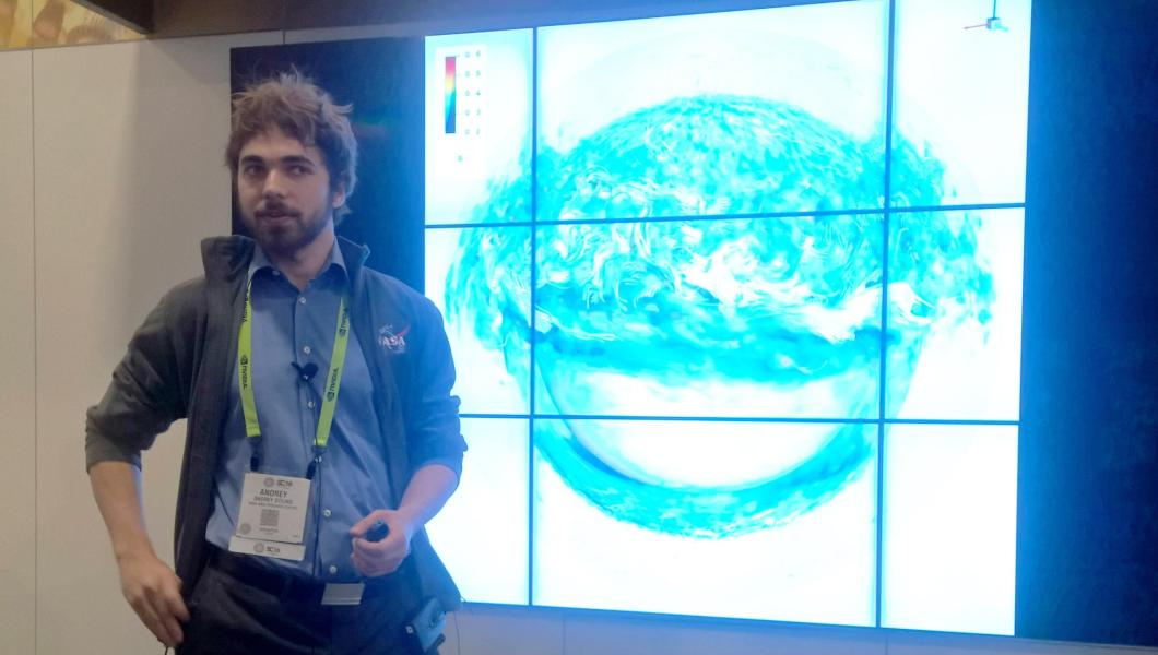 Ph.D. student Andrey Stejko speaking about his heliophysics research at SC16. The image on the screen is a detailed computer-generated visualization of the Sun's magnetic field.