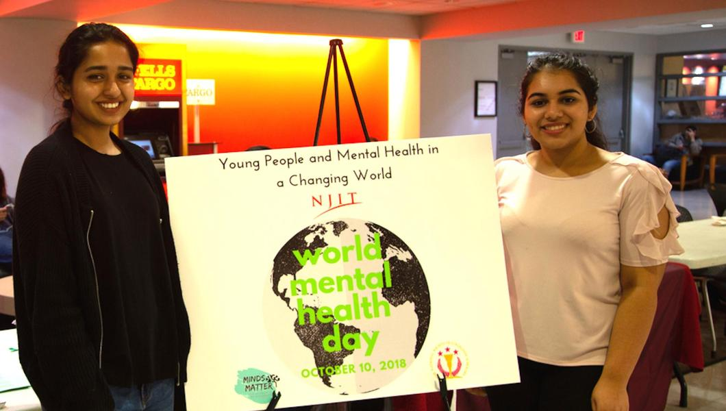 Mehak Farrukh, Minds Matter event planner (left), and Charu Arya, Minds Matter student president, publicize the new club and World Mental Health Day in the Campus Center.