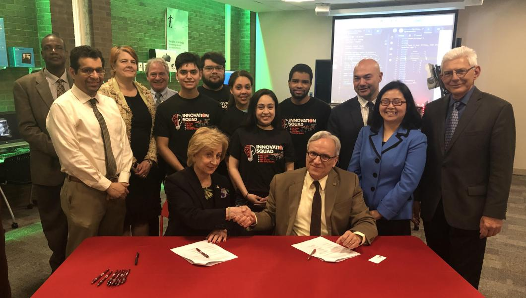 Maris Lown (seated left), vice president of academic affairs, Union County College, and Fadi P. Deek, provost and senior executive vice president, NJIT, shake on it after signing a joint academic agreement between the two institutions.