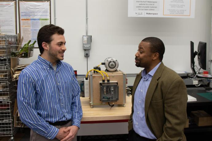 Matthew Berdel, a systems engineer and program trainee, and Professor ShaQueel Dyer describe the machine they built in class, complete with a machine frame, electrical enclosures, an AC motor, lockout-tag-out safety features and an LED light panel with switches.
