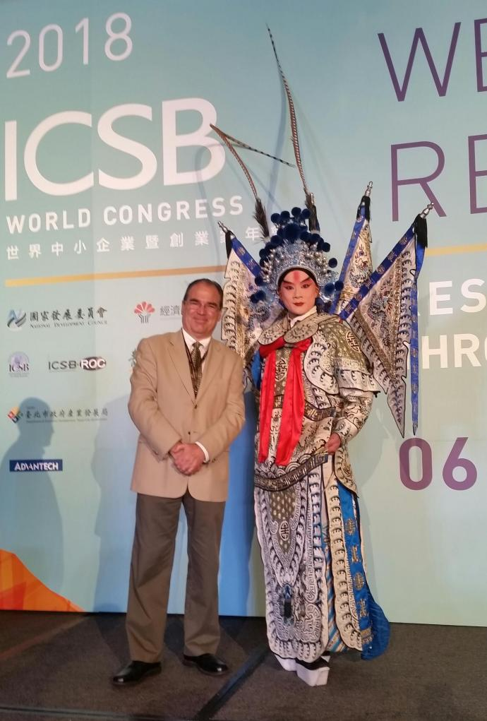 MTSM Associate Professor of Entrepreneurship Cesar Bandera with an ICSB Academy host dressed in local regalia