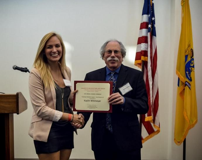 Dean Anthony Schuman presents first-year digital design student Kaylin Wittmeyer with the Freshman Portfolio Prize.
