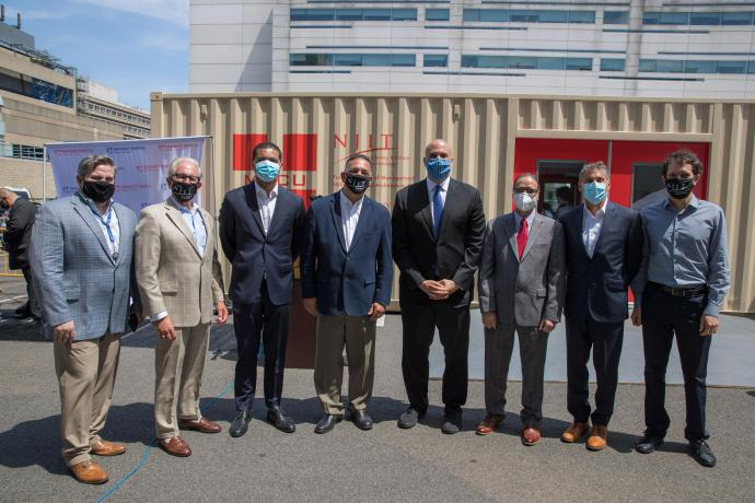 U.S. Senator Cory Booker (fifth from left) joins members of the New Jersey consortium that developed a mobile medical care unit from repurposed shipping containers to deploy to areas in need of health care infrastructure.