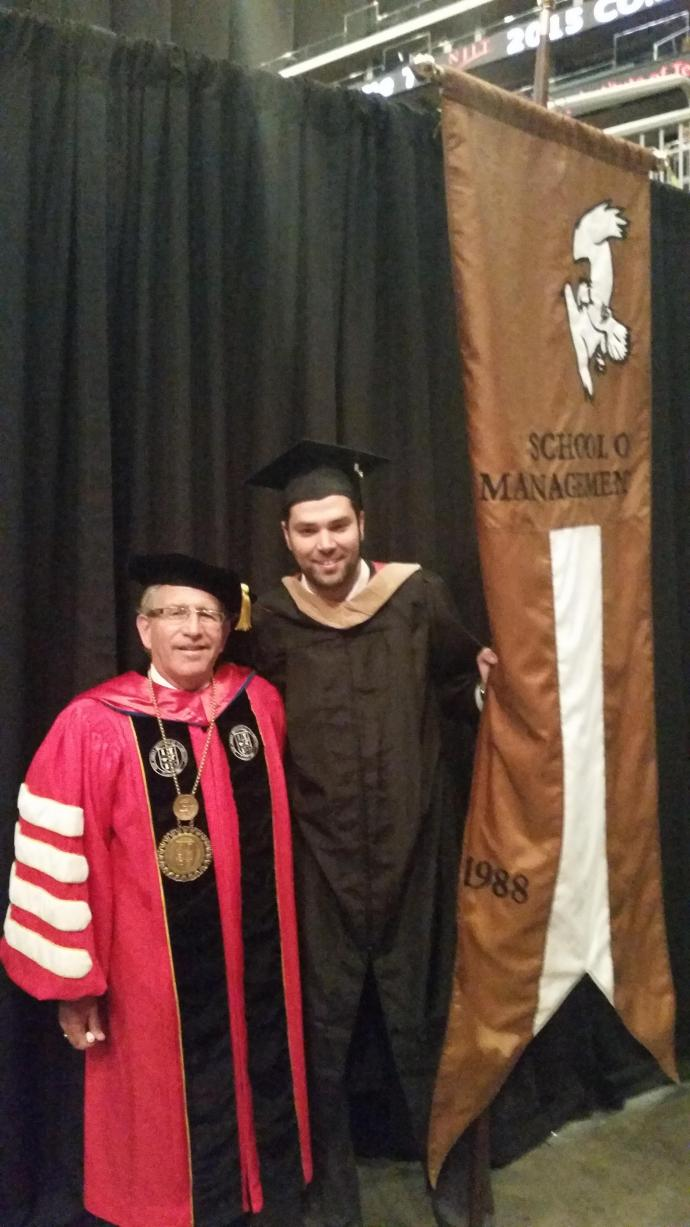 Rogerio Henriques (right), here with NJIT President Joel Bloom, carried the Martin Tuchman School of Management gonfalon at the 2015 graduation ceremony.