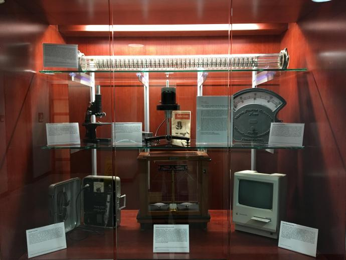 (Top Shelf) York-Scheibel Column; (Middle Shelf, Left) 1947 Bausch & Lomb optical microscope; (Middle-Center) Brookefield Viscometer; (Middle-Right) Weston Station Voltmeter; (Bottom Shelf, Left) Geiger Counter; (Bottom-Middle) 1954 Seederer-Kohlbusch Scale; (Bottom-Right) 1984 Apple Macintosh Plus.