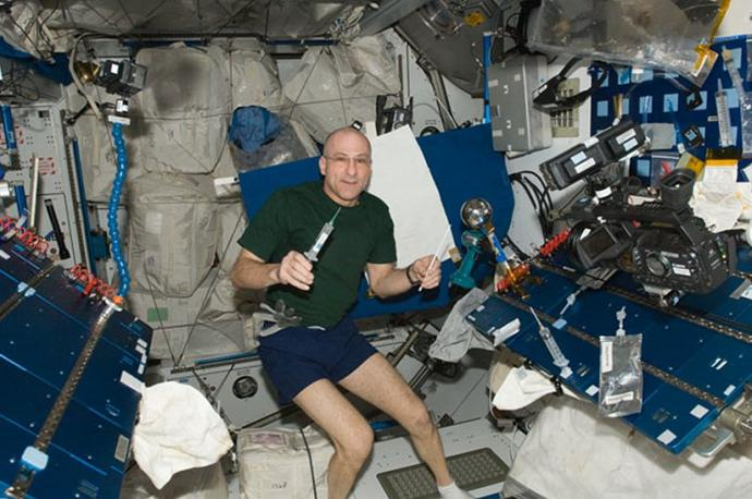 Astronaut Donald R. Pettit on board the International Space Station. To the right is the Van de Graaff generator that he improvised with Legos and used to electrify water droplets and gain new, important knowledge about Taylor cones in collaboration with