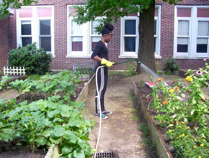 Recent STEM Academy graduate Renieal Campbell volunteers in the school's sustainable garden.