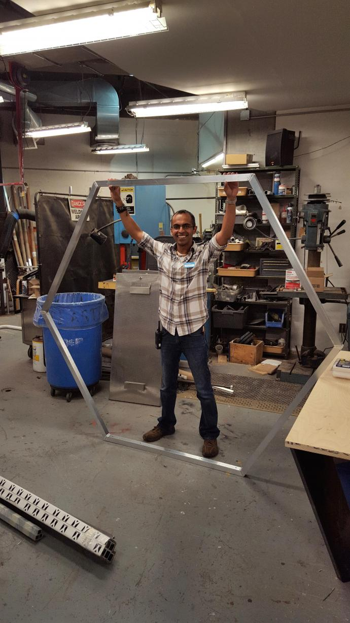 Deepesh Dhingra holds onto a hexagon drone race air gate that he and the exhibition team designed for the museum's Liberty Cup Drone Race for hobbyist drone pilots.
