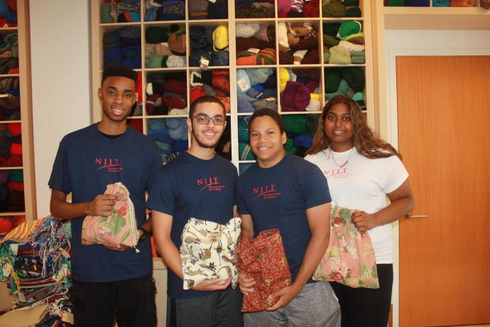 Cameron Bennett, Keith Montalvo, Brandon Chin and Kamela Chandrika preparing holiday gifts for mariners far from home.