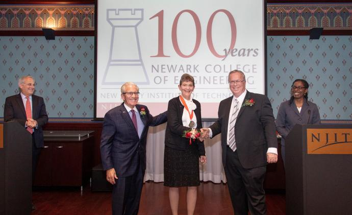 NCE 100 Honoree Ellen Pawlikowski with NJIT President Joel Bloom (near left) and NCE Dean Moshe Kam (near right). The presenters, NJIT Trustee Robert Cohen (left) and NCE Associate Dean for Research Janice Daniels (right), look on.