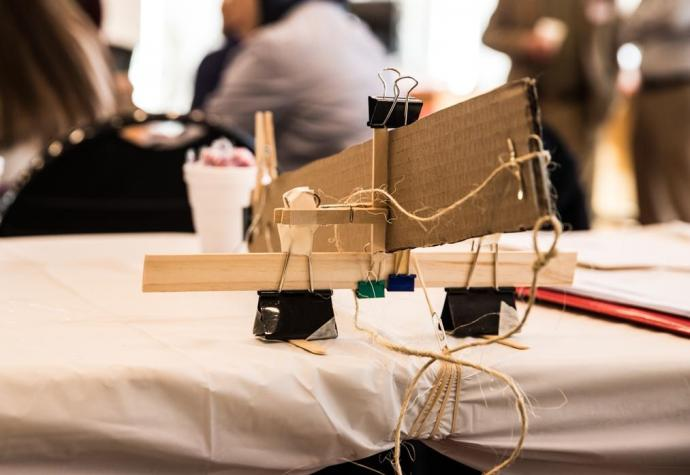 A robotic arm, built with cardboard, string and office clips